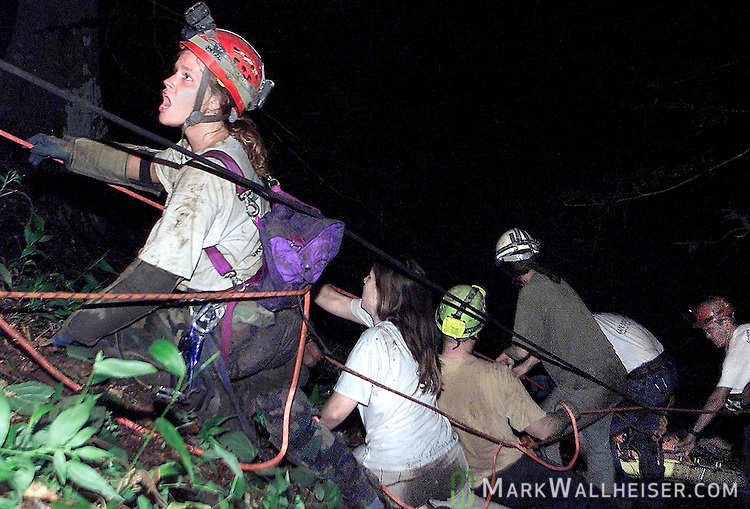 """Tracey Matzke (L), from Largo, yells to the top of the sink for them to """"pull hard"""" as her team on the lip of the 60 foot drop into Climax Cave pull and drag the litter carrying the body of 33 year old Bruce Brewer, of Tallahassee  at 4:30 am Monday morning after a 32 + hour rescue effort to recover the spelunker's body."""