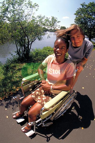 young woman pushing young woman in wheelchair