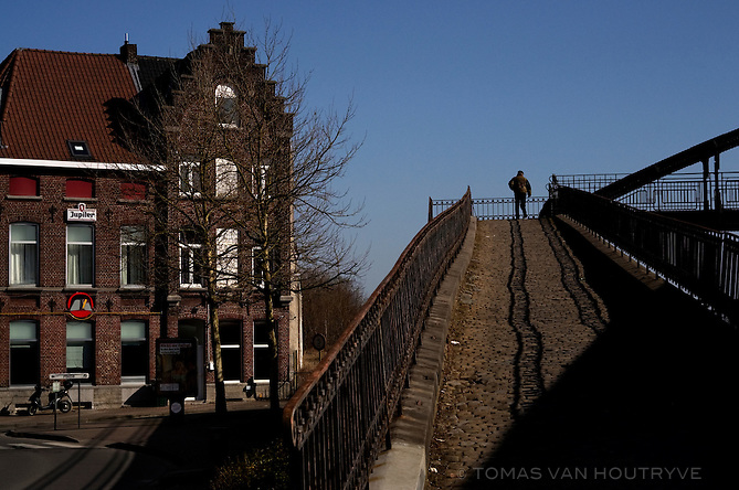 A man walks on a pedestrian overpass near the train station in Ronse, Belgium on March 5, 2013. Initially a bilingual city, Ronse became a center for Flemish nationalism and Dutch language activism in the early 20th century. The city with has retained a mixed language population, and demographics have changed with an influx of North African immigration. The city is located in Flanders near the language border.