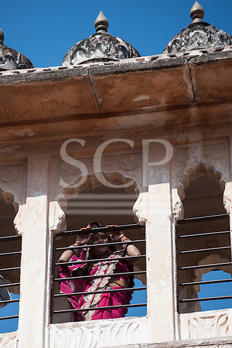 Jodhpur, India. Mehrangarh sandstone hill fort of the Marwar rulers. A woman in Rajasthan pink sari looking through a window.