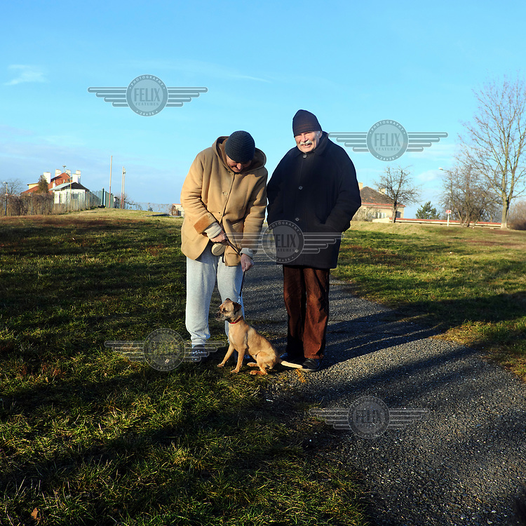 A couple out walking a dog.