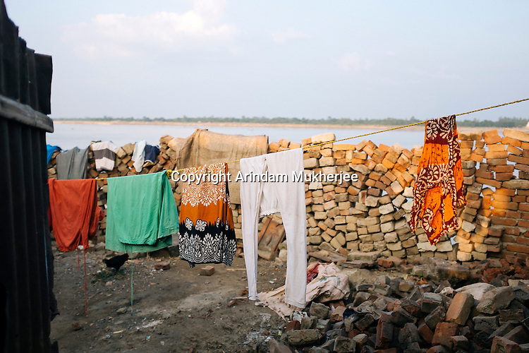 A house on the bank of Ganga. In the September2014 erosion this house was damaged and now a temporary wall is in place. Dhuliyan, Murshidabad District, West Bengal, India.