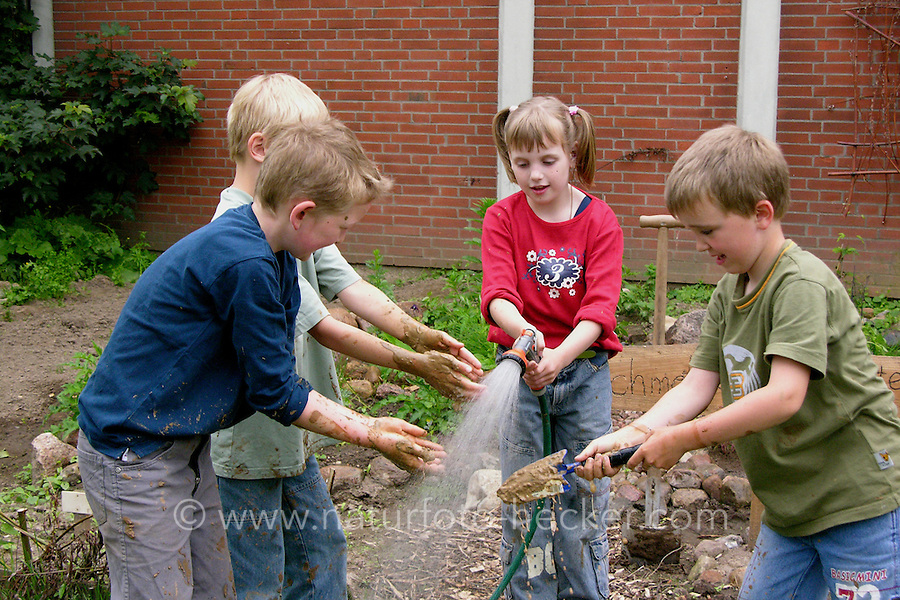 Lehmbackofen im Schulgarten, Garten der Grundschule Nusse wird als Projektarbeit von einer 1. Klasse gestaltet, Kinder bringen feuchten Lehm an einem Lehmbackofen an und waschen nun ihre lehmigen Hände, Gartenarbeit