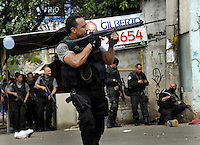 A policeman shoots his gun during a operation at Vila Cruzeiro slum, Rio de Janeiro, Brazil, November 25, 2010. Authorities in Rio de Janeiro try to control a fourth day of violence apparently orchestrated by drug gang members who have attacked police stations and burned cars in Rio de Janeiro city as protest by traffickers after being forced from their turf by police occupations of more than a dozen slums in the past two years..(Austral Foto/Renzo Gostoli)