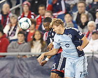 New England Revolution defender Darrius Barnes (25) and Sporting Kansas City defender Chance Myers (7) battle for head ball.  In the first game of two-game aggregate total goals Major League Soccer (MLS) Eastern Conference Semifinal series, New England Revolution (dark blue) vs Sporting Kansas City (light blue), 2-1, at Gillette Stadium on November 2, 2013.