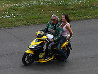 Jul. 20, 2014; Morrison, CO, USA; NHRA funny car driver John Force and wife Laurie Force riding a scooter on the return road during the Mile High Nationals at Bandimere Speedway. Mandatory Credit: Mark J. Rebilas-