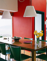 A crisp and contemporary interior is made inviting with the use of striking red in the dining area, which contrasts with the bold green dining chairs.