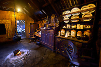 Original interior of the kitchen area with paet fire burning in The Blackhouse, 24 Arnol, Bragar, Isle of Lewis, Scotland.