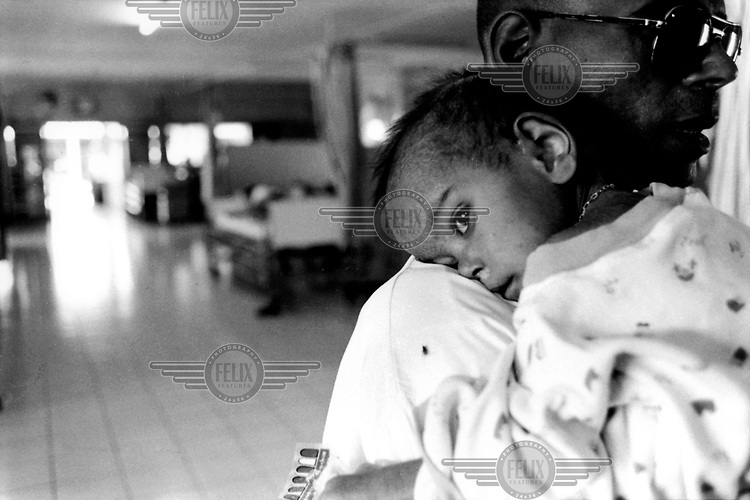 Volunteer worker caring for a child born with HIV. The child is now in the advanced stages of the disease. Wat Prah Bat Nam Thu, the first AIDS monastery-hospice in Thailand.