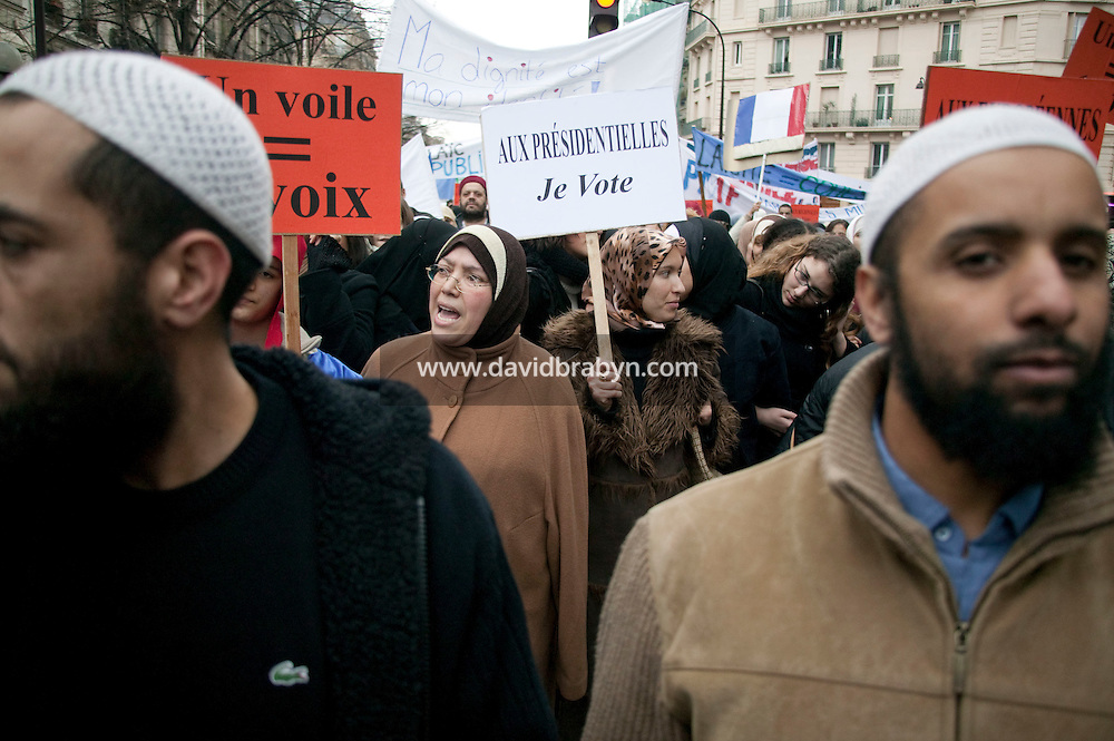 Men and women in Islamic head scarfs take part in a street protest in Paris, France, 17 January 2004, against a law that plans to restrict the wearing of veils in public schools.