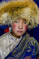 Nomad girl wearing fur hat in the Damda region, Kham, Tibet.<br /> From the plains of Mongolia, to the sands of Africa, and the outback of Australia, nomads evoke a sense of freedom, self-reliance and harmony in the often-harsh land around them. None have fascinated me more than the nomads of Tibet, a country that I have been visiting for more than twenty years. I look at the sunburned cheeks of this little girl and wonder at the tenacity it must take to live in such beautiful yet demanding environments and the delicate balance it takes for man, animal and landscape to coexist.