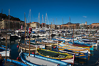Colorful Port Lympia fishing boats with old town and clocktower in the background under a blue sky, Nice, French Riviera (Côte d'Azur) France