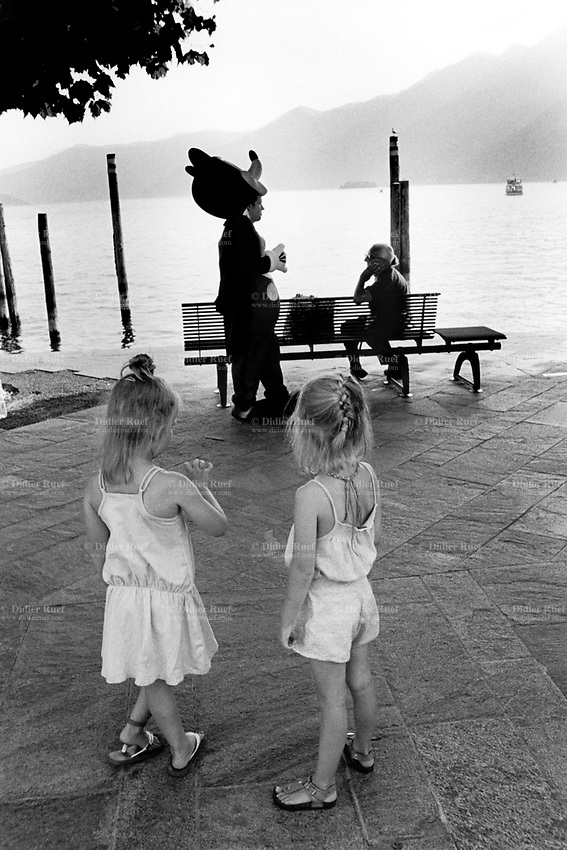 Switzerland. Canton Ticino. Ascona. The town is located on the shore of Lake Maggiore. A street artist dressed as Mickey Mouse talks to an old woman seated on a bench. Two young girls, both sisters, are waiting for the artist to start his live performance. Mickey Mouse is a funny animal cartoon character and the official mascot of The Walt Disney Company. An anthropomorphic mouse who typically wears red shorts, large yellow shoes, and white gloves. Lake Maggiore or Lago Verbàno is a large lake located on the south side of the Alps.1.08.2017  © 2017 Didier Ruef