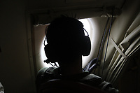 A member of the Japan Maritime Self Defence Force looks out of the window of a PC3 reconnaissance plane.