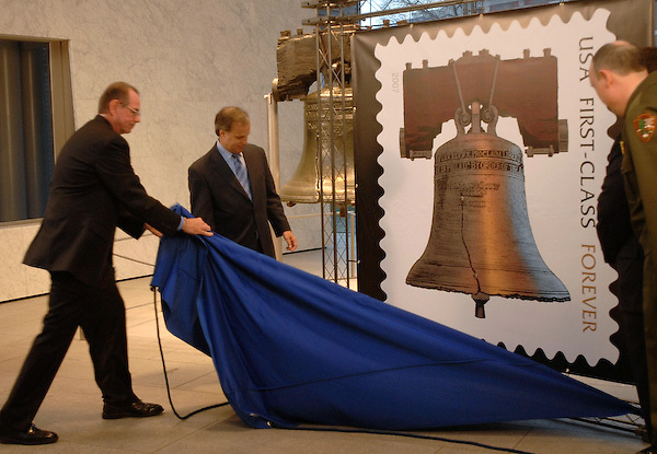 United States Postal Service spokesman Mark Saunders, left, wrestles the cover off the new Forever Stamp at ceremonies at the Independence National Historic Park's Liberty Bell pavilion with Alan Kessler, vice chairman of the USPS Board of Governors, center and the Park Service Superintendent Dennis Reidenbach, right, looking on Thursday, April 12, 2007, in Philadelphia. The first class stamp is good for mailing letters any time in the future regardless of price changes. (AP Photo/Bradley C Bower)
