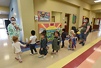 Teachers, including Katie Jennings (left), lead students through a hallway to a play area on Wednesday March 17 2021 at the Benton County Sunshine School and Development Center.<br />