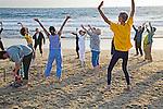 Senior men and women exercise on Playa del Rey beach, California at sunset in winter.