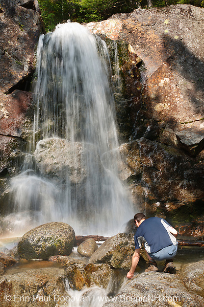 A hiker explores Thirteen Falls along Franconia Brook in the Pemigewasset Wilderness of <br /> Franconia, New Hampshire USA.