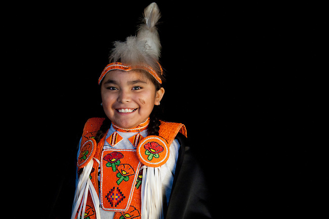 Fancy shawl dancer, TyLynne Kane  Northern Ute, in orange floral beadwork outfit next to black backdrop