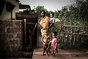 50 year old Bhanmati Mohanto is seen with her grand children outside her house at the Sansilo rehabilitation colony, set up by the TATA Steel company for the displaced families in Kalinganagar, Orissa, India. She sold 5 acres of her land to Tata for the proposed steel plant.