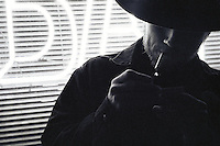 Man wearing cowboy hat lights a cigarette outside a bar at night. Black and white photography. Dallas Texas.