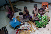 Talking before bedtime at the Doctors Without Borders (MSF; Medecins Sans Frontieres) tent compound. This compound is one of the few places children, known as Night Commuters, can find protection every  night to avoid being abducted by the Lords Resistance Army (LRA) in Northern Uganda. The LRA is primarily made up of abducted youth. Night Commuters find much more than safety in the compounds, they also find friendships, activity and fellowship. Tens of thousands of children, on average, make this exodus every evening. The war in Northern Uganda has been transpiring for two decades. Lachor, Gulu District, Uganda, Africa. December 2005 © Stephen Blake Farrington