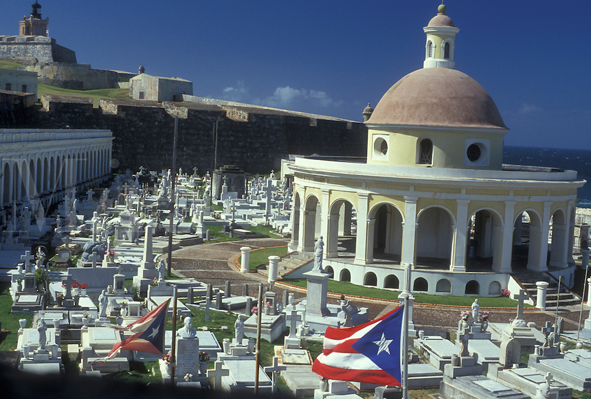 AJ2334, Puerto Rico, San Juan, Caribbean, Old San Juan, cemetery, Caribbean Islands, Porto Rico, The Puerto Rican flag flys in the foreground of San Juan Cemetery at the Fort San Felipe del Morro (El Morro Castle) in Old San Juan, Puerto Rico.