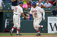 Wearing an Austin Senators throwback uniform, Round Rock Express designated hitter Manny Ramirez (39) is greeted by third base coach Spike Owen (11) after smashing a 2 run home run in the third inning of the Pacific Coast League baseball game against the Oklahoma City RedHawks on July 9, 2013 at the Dell Diamond in Round Rock, Texas. Round Rock defeated Oklahoma City 11-8. (Andrew Woolley/Four Seam Images)