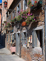 Flower boxes hang above entrance to shop in Chioggia Ital