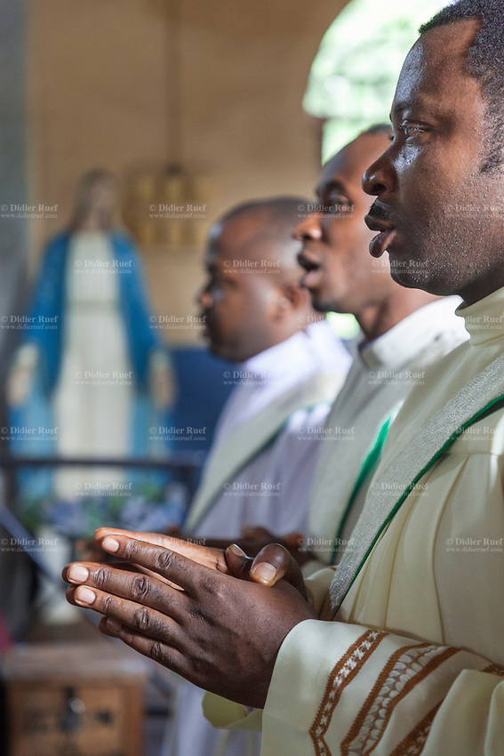 Nigeria. Enugu State. Awhun. Saint Luke's Catholic Parish. African Igbo catholic priests pray during the religious mass in honor of Reverend Father Clement Rapuluchukwu Ugwu, killed by burglars in his house on March 13th 2019. A plaster statue of the Virgin Mary stands up close to the wall. Mary was a first-century BC Galilean Jewish woman and the mother of Jesus, according to the New Testament. The gospels of Matthew and Luke in the New Testament describe Mary as a virgin; according to Christian theology she conceived Jesus through the Holy Spirit while still a virgin. Mary has been venerated since early Christianity and is considered by millions to be the most meritorious saint of the religion. She is said to have miraculously appeared to believers many times over the centuries. 11.07.19 © 2019 Didier Ruef