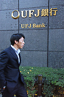 Businessmen pass the UFJ Bank in Tokyo's main business and financial district , Tokyo, Japan..
