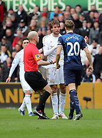 Pictured: Michael Dawson of Tottenham (R) has a go at Michu of Swansea (C) after his head clashed for a header against Scott Parker (not pictured) while match referee A Taylor (L) is trying to calm things down. Saturday 30 March 2013<br /> Re: Barclay's Premier League, Swansea City FC v Tottenham Hotspur at the Liberty Stadium, south Wales.