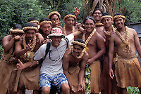 Tourist surrounded by smiling Polynesian dancers at a festival in Fatu Hiva, the Marquesas Islands