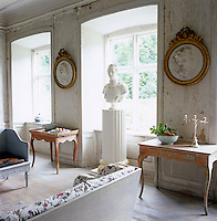 A pair of gilt-framed plaster medallions hangs on the worn walls of the second floor sitting room