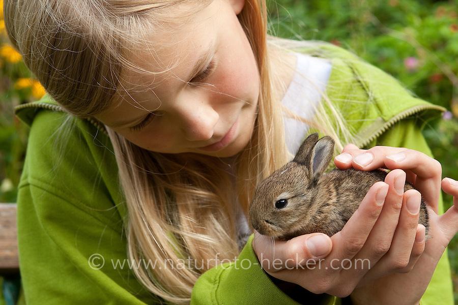 Wildkaninchen, Wild-Kaninchen, Kaninchen, verwaistes Jungtier wird in menschlicher Obhut großgezogen, Mädchen, Kind kuschelt mit Tierkind, Tierbaby, Tierbabies, Oryctolagus cuniculus, Old World rabbit