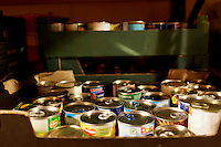Tins of fruit inside the store room of Hammersmith and Fulham food bank in Christ Church, Fulham. Volunteers meet customers, offering a hot drink and cake before an interview is carried out to assess the person's needs. After this specially-selected bags of food are made up. Many food banks are run in or by local churches though not all volunteers at this bank would describe themselves as regular church goers.