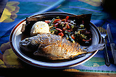 Costa Rica. Plate of food; grilled fish, broccoli, chillies, rice with vegetables.