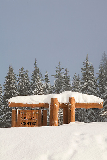 Deep snow at Lolo Pass nearly covering the Visitor Center sign on the border of Montana and Idaho