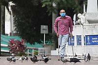 CALI - COLOMBIA, 14-04-2020: Un hombre en muletas va por el centro de la ciudad de Cali durante el día 22 de la cuarentena total en el territorio colombiano causada por la pandemia  del Coronavirus, COVID-19. / A man in crutches walks through the center of Cali during the day 22 of total quarantine in Colombian territory caused by the Coronavirus pandemic, COVID-19. Photo: VizzorImage / Gabriel Aponte / Staff
