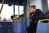 A schoolboy listens to music through headphones on a bus in Cricklewood, London.