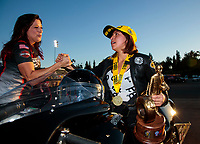 Nov 17, 2019; Pomona, CA, USA; NHRA pro stock motorcycle rider Jianna Salinas is congratulated by Angelle Sampey as she celebrates after winning the Auto Club Finals at Auto Club Raceway at Pomona. Mandatory Credit: Mark J. Rebilas-USA TODAY Sports