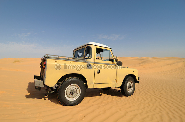 Africa, Tunisia, nr. Tembaine. Desert traveller Frank driving his 1964 Land Rover Series 2a Truck Cab through a sandfield close to Tembaine on the eastern edge of the Grand Erg Oriental. --- No releases available, but releases may not be needed for certain uses. Automotive trademarks are the property of the trademark holder, authorization may be needed for some uses.  --- Info: Image belongs to a series of photographs taken on a journey to southern Tunisia in North Africa in October 2010. The trip was undertaken by 10 people driving 5 historic Series Land Rover vehicles from the 1960's and 1970's. Most of the journey's time was spent in the Sahara desert, especially in the area around Douz, Tembaine, Ksar Ghilane on the eastern edge of the Grand Erg Oriental.