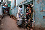 An Indian Milk man with his customer at a lane in Varanasi, Uttar Pradesh, India.