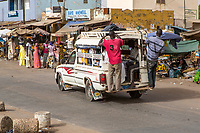 Senegal, Touba.  Local Transport.  Pick-ups with Young Men usually Hanging on the Back Running Board, Passengers Inside.