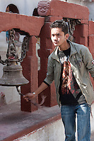 Bodhnath, Nepal.  Young Nepali Man Rings a Bell near the Entrance to a Shrine  adjacent to the Stupa of Bodhnath.