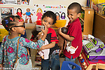 Education preschool 3 year olds pretend play area girl in dressup glasses hoding camera to take picture of two boys holding dolls