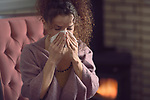 Sick with cold young woman blowing her runny nose or sneezing in a paper tissue sitting at home by a fireplace wearing warm clothes