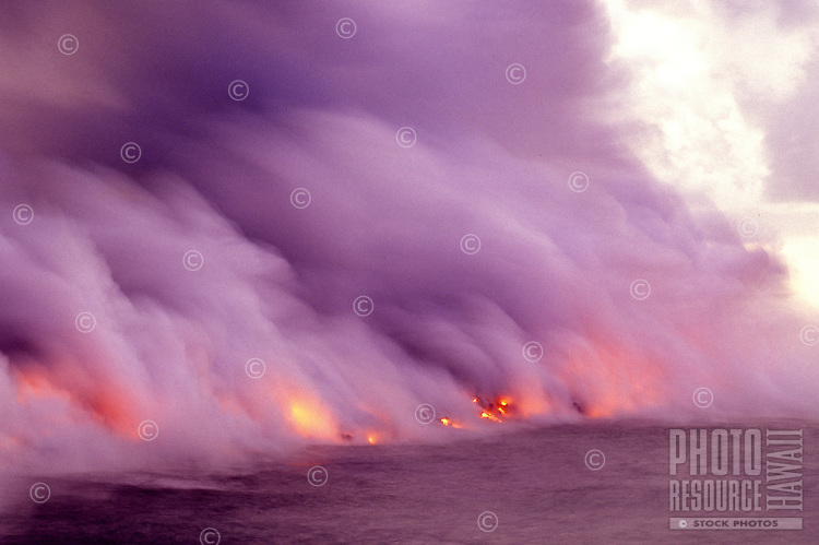 Gigantic steam clouds rise from a fiery lava streaming into the sea off the Puna coast on the Big Island of Hawaii.