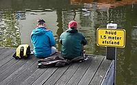 Nederland - Amsterdam- 2020.   Twee mannen op een steiger aan de gracht. Bord met de tekst: Houd anderhalve meter afstand.  Foto ANP / Hollandse Hoogte / Berlinda van Dam