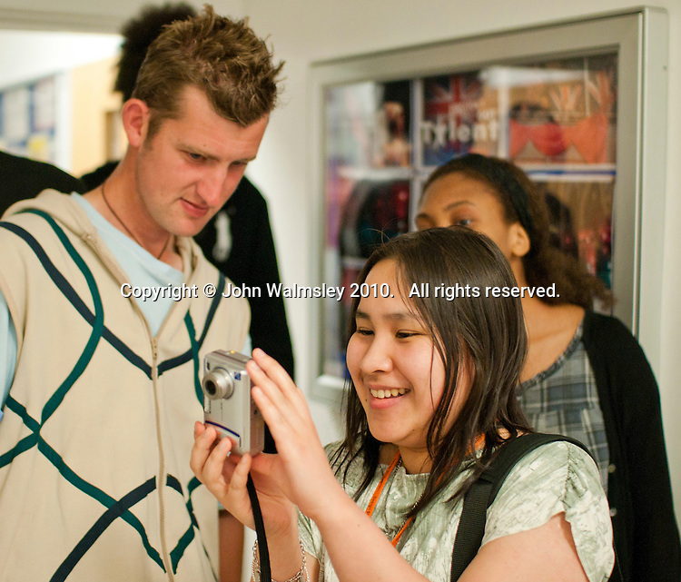 Fashion student photographs a model wearing her designs, Fashion Show at Further Education College.  Clothes designed for and modelled by Special Olympics Athletes.  Clothes designed by year 1 BTEC National Diploma Fashion and Clothing students.